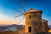 Windmills on the Greek island of Patmos. Patmos is a small Greek island in the Aegean Sea, most famous for being the location of both the vision of and the writing of the Christian Bible's Book of Revelation. One of the northernmost islands of the Dodecanese complex, Patmos' main communities are Chora (the capital city), and Skala, the only commercial port. Other settlements are Grikou and Kampos. The churches and communities on Patmos are of the Eastern Orthodox tradition.
