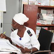 INDIVIDUAL(S) PHOTOGRAPHED: Adigun Abiola. LOCATION: Lagos State University Teaching Hospital Dot Clinic, Lagos, Nigeria. CAPTION: As head pharmacy nurse, Adigun Abiola must carefully check that the hospital's pharmacy is properly stocked.