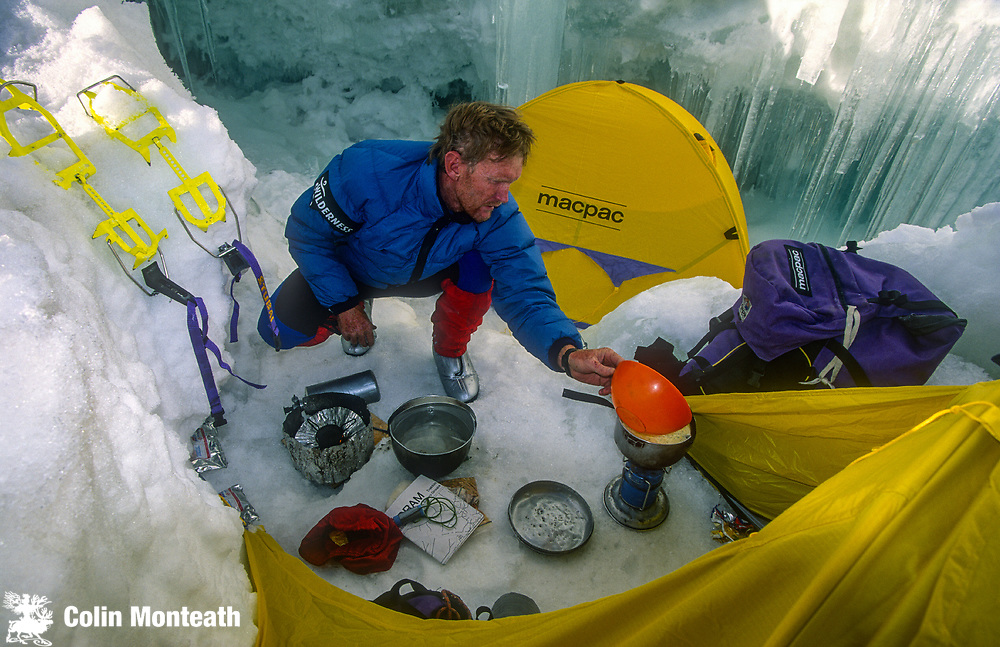 Climber prepares dinner in shelter of crevasse on 7300m peak 1st ascent Chongtar, Karakoram Mts, far western China, Central Asia