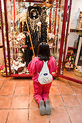 05 NOVEMBER 2004 - MEXICO CITY, MEXICO: Patricia Herrera, a devotee of Santa Muerta (St. Death) prays to the saint in Iglesia de la Piedad (Mercy Church) in the Tepito section of Mexico City. St. Death is venerated throughout Mexico and Mexican communities in the United States. The veneration of St. Death started in Mexico's prisons about 10 years and has since spread through working class neighborhoods in many Mexican cities. The worship St. Death was recognized as an official by the Mexican government in 2003. The Catholic Church in Mexico is opposed to the worship of St. Death and has held rallies and prayer vigils against the Saint. The small church in Tepito is frequently swamped with visitors and the religion has spread quickly through the tough, drug and crime plagued neighborhood, widely considered the most lawless in Mexico City.  PHOTO BY JACK KURTZ