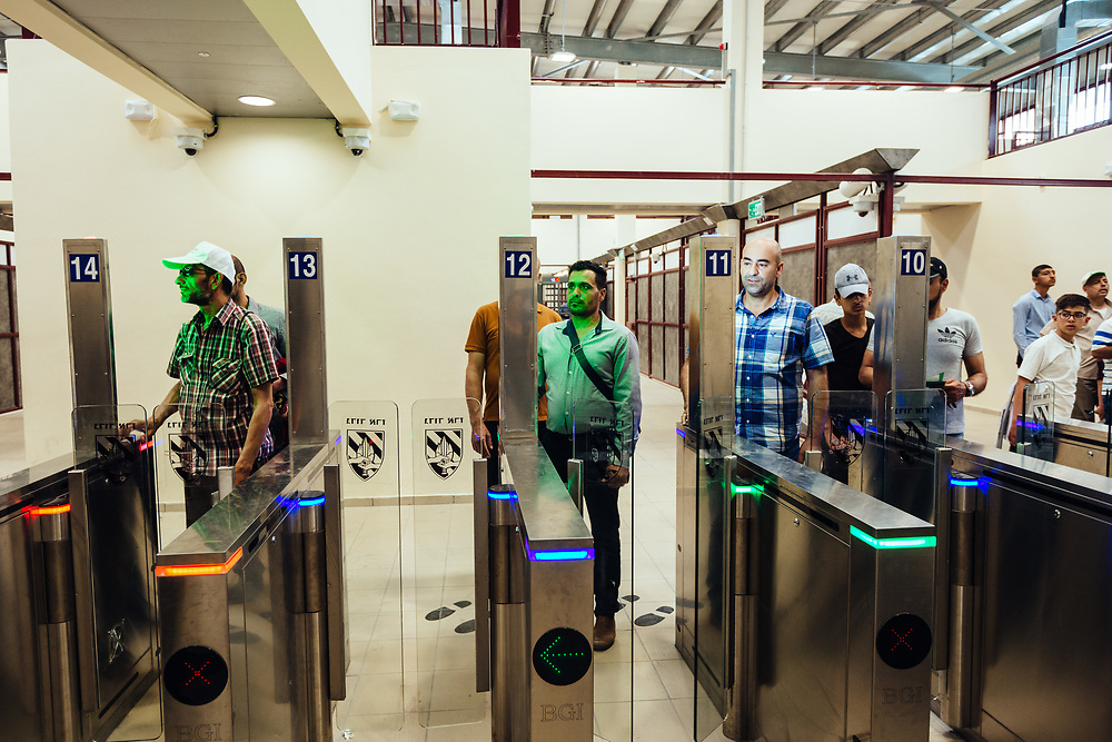 Palestinians use a biometric card at an automated gate equipped with a facial recognition system, as they cross Qalandiya checkpoint, south of Ramallah, West Bank, on May 17, 2019. Israeli authorities are introducing biometric border crossing systems at West Bank checkpoints, thus minimizing the interaction between Israeli soldiers and Palestinians crossing into Israel.