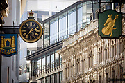 Ornate company logos of Banking institutions' street signs - incl TSB, left - on the narrow medieval Lombard Street in the heart of the capital's financial district. A cat and fiddle with an ornate clock are with the background of more modern architecture. Such hanging signs were banned by Charles II, but replicas were erected for the coronation of Edward VII in 1902.