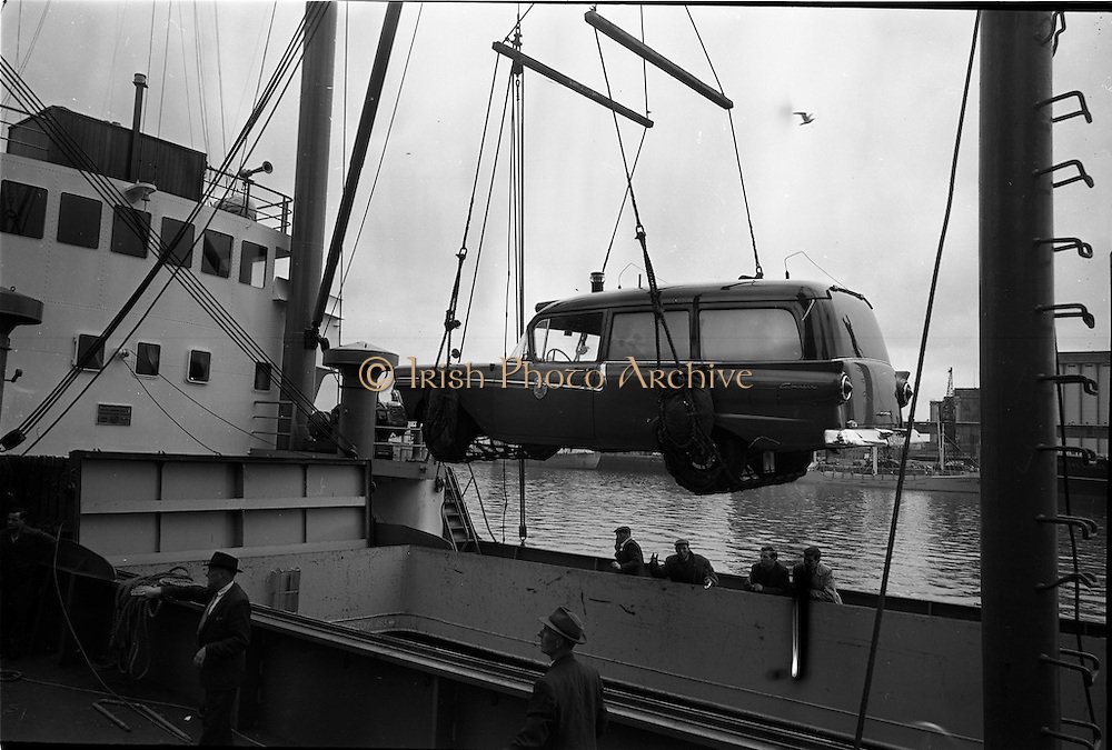 """25/06/1963<br /> 06/25/1963<br /> 25 June 1963<br /> Ford station wagon Ambulance being unloaded from the ship the """"City of Cork"""" at the North Wall, Dublin port. Image shows the ambulance being hoisted from the ship's hold by the ship's derrick."""