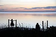 Visitors watch a sunset over Lake Apopka from a boat dock at Magnolia Park, Monday, Jan. 16, 2017, in Apopka, Fla. (Phelan M. Ebenhack via AP)
