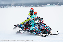 Motorcycle riding instructor Oksana Voevodina of St. Petersburg having fun on a snowmobile with a friend at the Baikal Mile Ice Speed Festival as competitors parade on the 3-feet of ice that covers Lake Baikal every winter. Maksimiha, Siberia, Russia. Saturday, February 29, 2020. Photography ©2020 Michael Lichter.