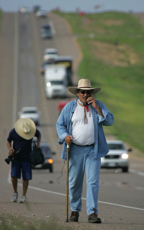 Jay Johnson Castro conducts one of many phone interviews while walking down Highway 83 on the outskirts of Laredo on Tuesday, October 10, 2006.  Castro said he was walking over 200 miles from Laredo to Brownsville to protest the proposed border wall along the Rio Grande.