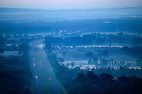 overhead view of morning fog in the valley around a highway and small town with traffic and water tower