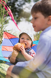 Little baby boy eating croissant sitting with his brother on meadow in the countryside, Bavaria, Germany