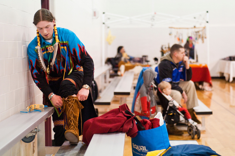 """Matt Dixon   The Flint Journal..Jeff, 23, from Oxford ties his boot in between dances during a powwow organized by the Great Lakes Indian Culture Association at Baker College, Sunday, March 13. """"I Dance not only because I. like to do it but for my family's health"""" said Jeff. Some dances and songs are similar to prayers in Indian culture."""