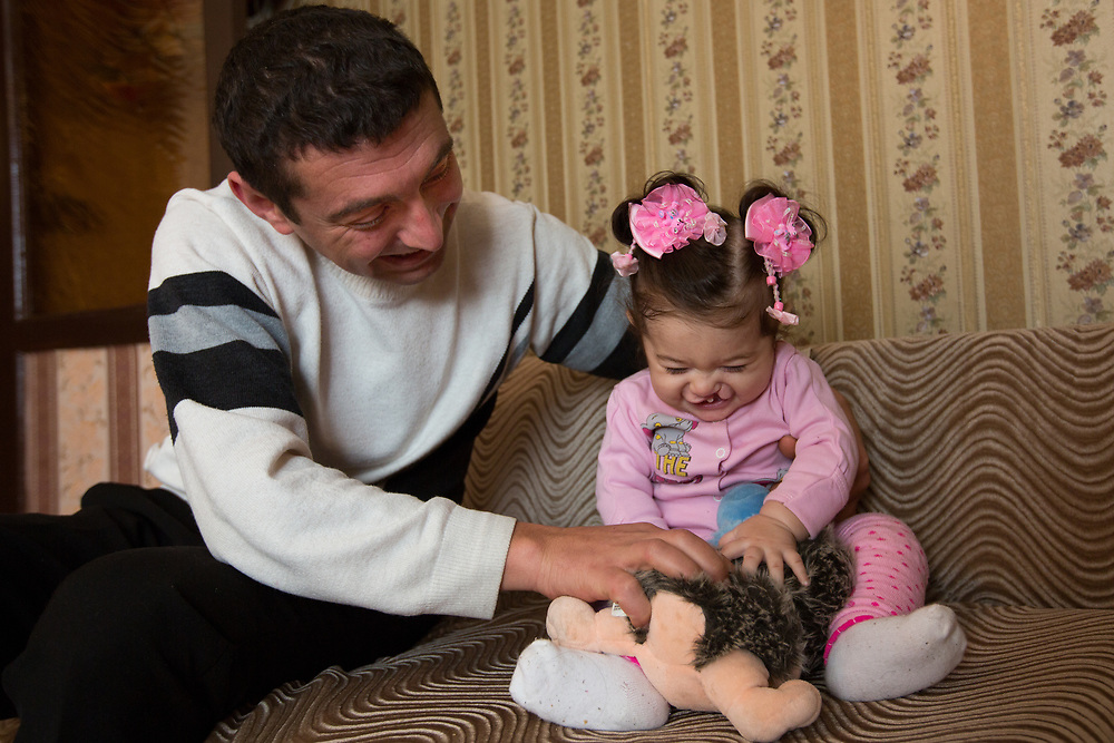 CAPTION: Stella's father Arman plays with her and her soft toys. In summer 2013, he visited Dr Fomenko to enquire about whether surgery could be possible for his daughter without insurance. She reassured him that she could operate on her, as SmileTrain could support it. LOCATION: Volgograd, Russia. INDIVIDUAL(S) PHOTOGRAPHED: Arman Aharonyan (left) and Stella Aharonyan (right).