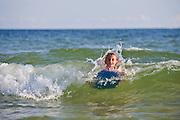 A girl boogie boards in the ocean in Fort Morgan, Alabama.