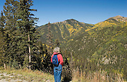 Woman hiker views aspens on mountains above Taos Ski Valley, New Mexico<br />