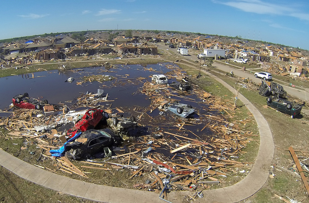 A pile of destroyed cars of teachers lie in the pond next to Briarwood elementary school in Oklahoma City, Oklahoma May 22, 2013.  Rescue workers with sniffer dogs picked through the ruins on Wednesday to ensure no survivors remained buried after a deadly tornado left thousands homeless and trying to salvage what was left of their belongings. Curvature of horizon in the photo is due to an ultra-wide angle lens.  REUTERS/Rick Wilking (UNITED STATES)
