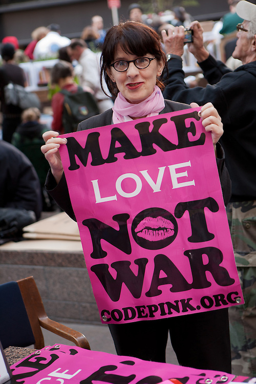 """A woman from Code Pink, a woman-initiated peace movement, holds a bright pink sign that reads """"Make love not war."""""""