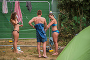 Washing facilitieas are basic and crowded, so some find a corner to do it themselves - The 2017 Glastonbury Festival, Worthy Farm. Glastonbury, 25 June 2017