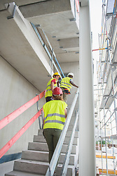 Construction workers climbing upstairs at building site, Munich, Bavaria, Germany, Europe
