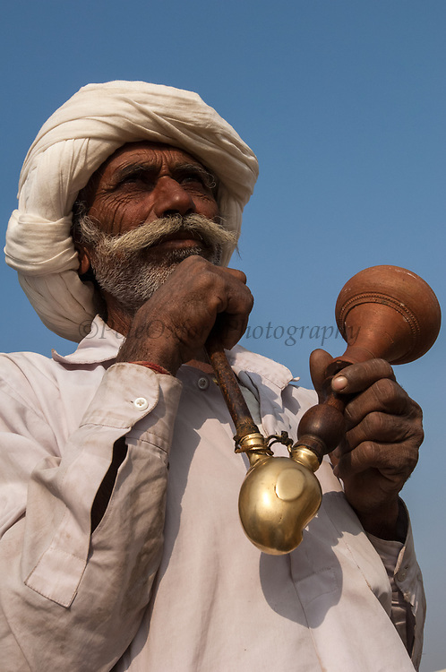 Rajusthani pastoralist smoking pipe or bong at the Pushkar camel and livestock fair which takes place in the Hindu month of Kartik (October / November) ten days after Diwali (Festival of Lights).  They usually wear cotton dhoti (strip of fabric tied into pants), cotton jacket and white cotton turban.<br /> Pushkar has always been the the region's main market for herdsman and farmers buying and selling camels, horses, indigenous breeds of cattle and even elephants. Over the years this annual trading event has increased in volume to become one of the largest in Asia. Temporary tents and campsites suddenly appear to accomodate the thousands of pilgrims, villagers and tourists. Entertainers and contests abound and a festive funfair atmosphere prevails over Pushkar during the Mela's 2 week duration. Thousands of men come first with their camels, horses and cattle and camp on the dunes to transact business. 3 days before the full moon the women arrive beautifully attired. The town of Pushkar is one of the holiest centers of Hinduism and houses one of the few Brahma Temples in India. It is one of the 5 essential pilgrimage centers which a Hindu must visit in his lifetime along with Badrinath, Puri, Rameshwaram and Dwarka. The 12 day fair culminates in a religious Hindu pilgrimage and reaches a crescendo on the night of the full moon (Purnima) when pilgrims take a dip in the holy lake.  <br /> Pushkar, Rajasthan. INDIA