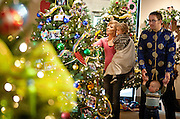 The Giddings family looks through the Christmas tree exhibition during the Winter Market at the Utah Cultural Celebration Center, Saturday, Dec. 1, 2012.