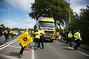 13 local activists locked themselves in specially made arm tubes to block the entrance to Quadrillas drill site in New Preston Road, July 03 2017, Lancashire, United Kingdom. A truck owned by local Pete Marquis is attempted stopped by activists. The activists included 3 councillors; Julie Brickles, Miranda Cox and Gina Dowding and Nick Danby, Martin Porter, Jeanette Porter,  Michelle Martin, Louise Robinson,<br /> Alana McCullough, Nick Sheldrick, Cath Robinson, Barbara Cookson, Dan Huxley-Blyth. The blockade is a repsonse to the emmidiate drilling for shale gas, fracking, by the fracking company Quadrilla and part of an ongoing struggle where makeshift towers and makeshift camps have sprung up outside the premisses. Lancashire voted against permitting fracking but was over ruled by the conservative central Government. All the activists have been active in the struggle against fracking for years but this is their first direct action of peacefull protesting. Fracking is a highly contested way of extracting gas, it is risky to extract and damaging to the environment and is banned in parts of Europe . Lancashire has in the past experienced earth quakes blamed on fracking.
