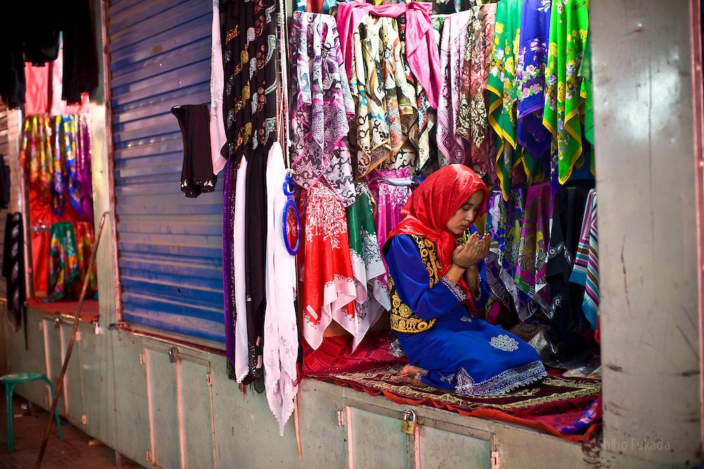 An Uighr girl prays at market in Hotan, Xinjian province in China.
