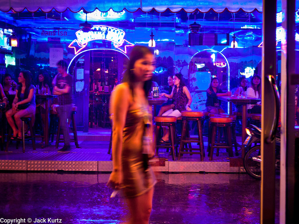 """12 JULY 2011 - BANGKOK, THAILAND: A woman walks past the """"Corner Bar"""" during a rain storm on Soi Cowboy in Bangkok. Soi Cowboy is a """"red light"""" district that is home to several brothels and """"short time"""" hotels that charge by the hour for their rooms. Prostitution in Thailand is illegal, although in practice it is tolerated and partly regulated. Prostitution is practiced openly throughout the country. The number of prostitutes is difficult to determine, estimates vary widely. Since the Vietnam War, Thailand has gained international notoriety among travelers from many countries as a sex tourism destination. One estimate published in 2003 placed the trade at US$ 4.3 billion per year or about three percent of the Thai economy. It has been suggested that at least 10% of tourist dollars may be spent on the sex trade. According to a 2001 report by the World Health Organisation: """"There are between 150,000 and 200,000 sex workers (in Thailand).""""  PHOTO BY JACK KURTZ"""