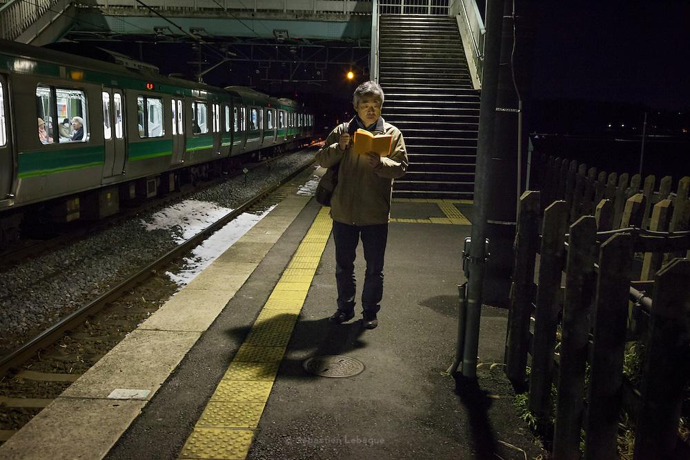 JAPAN, NARITA - 13 JANUARY 2013 -  A man read a book in the station of Shimoza Manzaki near Narita [FR] A homme lit un livre dans la gare de Shimoza Manzaki proche de Narita
