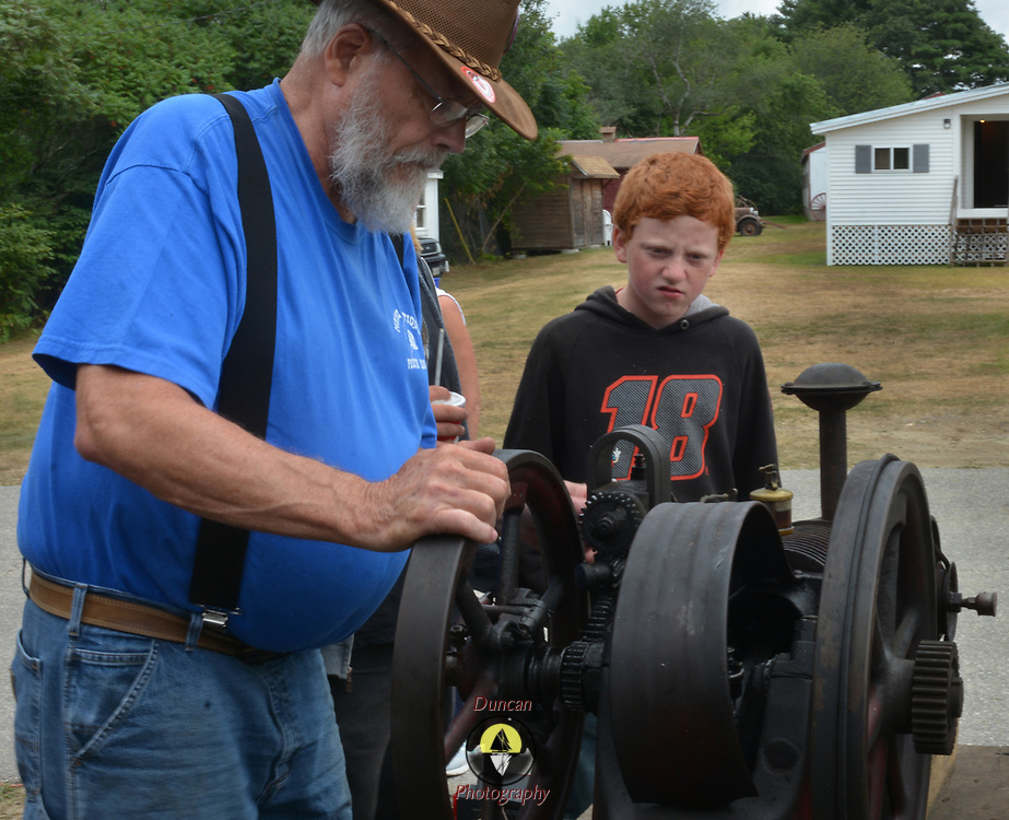 TOPSHAM, Maine- 8/8/17 -- Russ Welch of Arundel, Maine  describes the operation of a one-cylinder engine to Thomas Hughes of Monmouth at the Topsham Fair on Tuesday. Welch is part of the Maine Antique Power Association, dedicated to preserving powered tools which ran Maine's many farms prior to WWII.  The fair is open now and closes on Sunday, August 13.  Photo by Roger S. Duncan for the Forecaster.