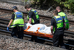 © Licensed to London News Pictures. 18/06/2018. London, UK. Police carry a body away from the train tracks near Loughborough Junction station after three bodies were discovered after they were reportedly hit by a train. Photo credit: Rob Pinney/LNP
