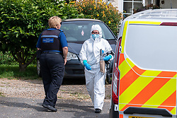 © Licensed to London News Pictures. 27/07/2021. Stoke Poges, UK. A forensic investigator gathers evidence at a property on Bells Hill in Stoke Poges, Buckinghamshire, following an assault on Monday 26 July at approximately 21:30BST. A man in his twenties suffered a serious leg injury following the assault which is understood to have involved a machete. Two men, aged 19 and 21, and a 20-year-old woman have been arrested on suspicion of section 18 wounding with intent. Photo credit: Peter Manning/LNP