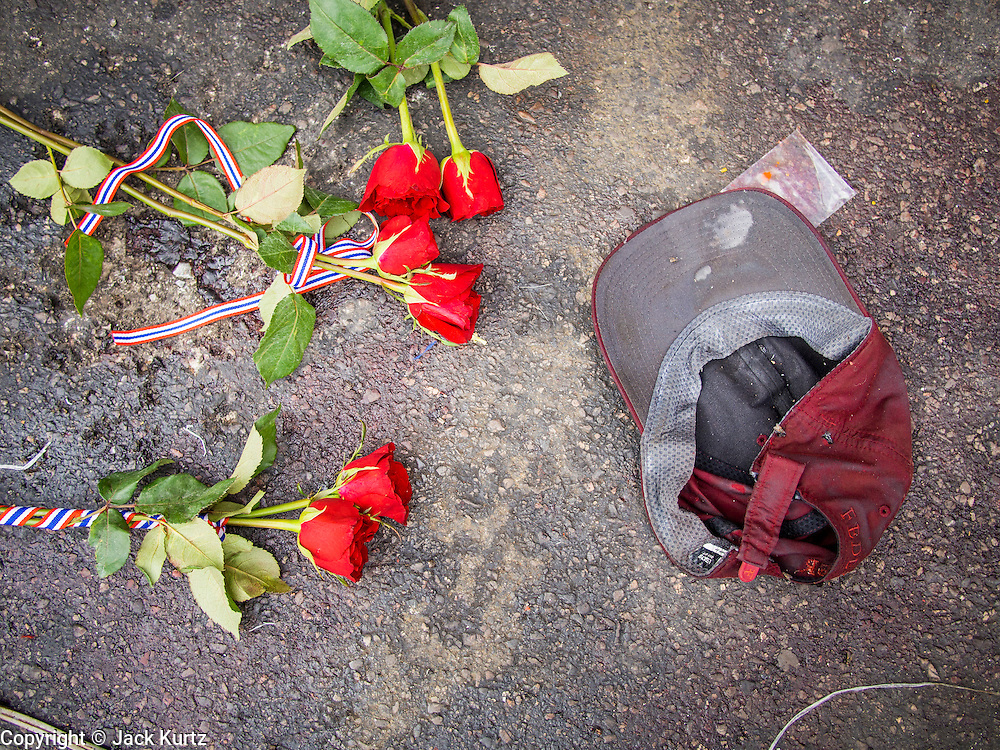 24 FEBRUARY 2014 - BANGKOK, THAILAND: Roses left by mourners on the ground next to a bloody hat worn by the victim of a grenade attack on anti-government protestors at the Ratchaprasong intersection in Bangkok. At least four people, three of them children, were killed in political violence over the weekend in Thailand. One in Trat province, near the Cambodian border, and three in Bangkok, at the Ratchaprasong protest site. At the Ratchaprasong site a grenade was fired into a crowd killing a child and an adult. A second child, injured in the blast, died overnight in a Bangkok hospital.   PHOTO BY JACK KURTZ