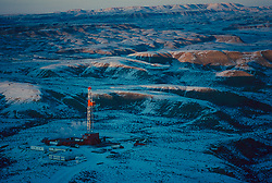 Stock photo of an on-shore drilling site in a snowy mountainous area