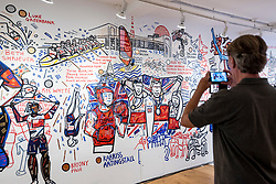 © Licensed to London News Pictures. 07/08/2021. LONDON, UK.  A visitor views Ben Mosley's wall mural focused on the achievement of Team Great Britain (GB) athletes at the Tokyo Olympics 2020.  Based at the pop-up Team GB Studio in Carnaby Street, the artist updates his mural daily with athletes' successes. The final day's events and closing ceremony are the only work remaining. Team GB has become the first to adopt non-fungible tokens (NFTs) featuring the athletes' previous achievements, which can be purchased through a dedicated store.  Photo credit: Stephen Chung/LNP