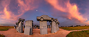 "Carhenge sunrise. Carhenge replicates England's Stonehenge using vintage American automobiles, near Alliance, Nebraska, in the High Plains region, USA. After studying Stonehenge in England, years later, Jim Reinders recreated the physical size and placement of Stonehenge's standing stones in summer 1987, helped by 35 family members. Reinders said, ""It took a lot of blood, sweat, and beers."" Carhenge was built as a memorial to Reinders' father. 39 automobiles were arranged in the same proportions as Stonehenge with the circle measuring a slightly smaller 96 feet (29m) in diameter. Some autos are held upright in pits five feet deep, trunk end down, while other cars are placed to form the arches and welded in place. All are covered with gray spray paint. The heel stone is a 1962 Cadillac. Reinders donated Carhenge to the Friends of Carhenge, who gifted it to the Citizens of Alliance in 2013. Additional sculptures have been erected in the Car Art Reserve, where Reinders' ""Ford Seasons"" is comprised of four Fords, inspired by Vivaldi's Four Seasons. Also, 29-year-old Canadian Geoff Sandhurst sculpted a spawning salmon. This image was stitched from multiple overlapping photos."