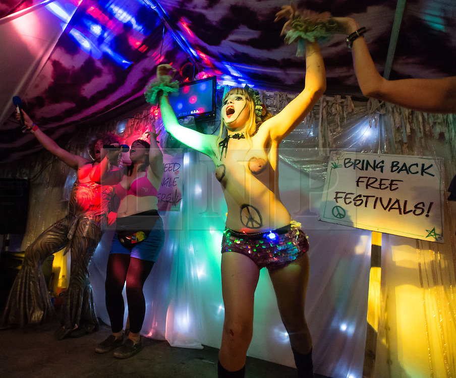 © Licensed to London News Pictures. 27/06/2015. Pilton, UK.  Night-time festival atmosphere at Glastonbury Festival 2015 in the Shangri-La area of the festival - festival goers and performers on stage at the Kamikaze Karaoke bar.  On Saturday Day 4 of the festival.  Shangri-La is a destroyed dystopian pleasure city.  This years headline acts include Kanye West, The Who and Florence and the Machine, the latter being upgraded in the bill to replace original headline act Foo Fighters. Photo credit: Richard Isaac/LNP