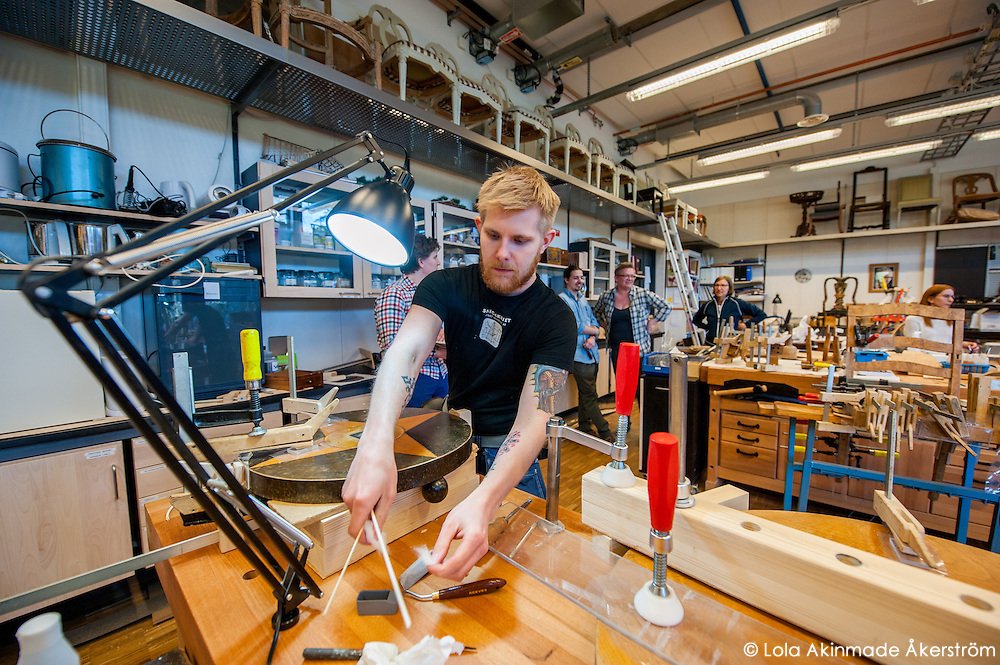A cabinetmaking student working on and polishing slabs of wood and stone.