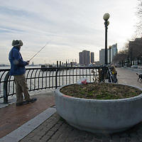 A man fishes in New York City's East River while his dog investigates the territory.