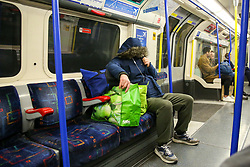 © Licensed to London News Pictures. 13/03/2020. London,  UK. A commuter covers his face with a coat hood on a nearly empty Piccadilly Line train. A tube driver has been tested positive of Coronavirus. 798 cases have been tested positive and ten patients have died from the virus in the UK. Photo credit: Dinendra Haria/LNP