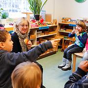 NLD/Amstrdam/20130123 - Nationale Voorleesdag op de basisschool Corantijn te Amsterdam, Minister van Onderwijs Jet Bussemaker eet een krentebol met de kinderen