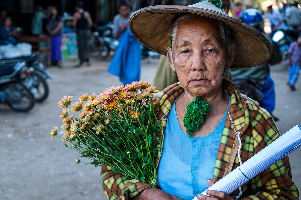 BAGAN, MYANMAR - CIRCA DECEMBER 2013: Old Burmese woman walking in the streets of  Nyaung U market close to Bagan in Myanmar with some flowers.