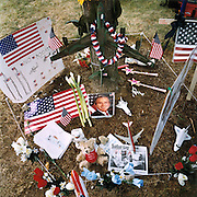 """Patriotic Americana - After 9/11. American icons dislayed beneath a tree near the Pentagon. In the week after the September 11th attacks, America sought to express their anger and patriotic unity. A smiling portrait of President Bush is surrounded by icons of American achievement, including a garlanded B52 bomber, placed as a makeshift memorial overlooking the charred Pentagon building, Washington DC. """"President Bush is a great Christian.. the angels are looking after him and America."""" - As quoted from a Washington citizen."""