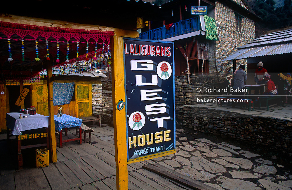A guest house sign near Ulleri on the Annapurna Sanctuary trekking route in central Nepal. Locals meet at a table for morning tea and the sign advertises Laligurans Guest House, a well-built house on the popular route for travellers from around the world. <br /> Communities here partly-depend on the agriculture of rice-growing but also on the passing tourist trade. Western trekkers from all over the world walk through these tiny communities on their way up the series of climbing trails of the Annapurna Conservation Sanctuary circuit, a sometimes rigorous walk from the low hills of Pokhara to the higher altitudes of Annapurna, the (26,000 feet (8,000 metre) peak. To be greeted by so much choice is the most rewarding experience and the offer of hot showers and great food is about the best reward for so much exertion.