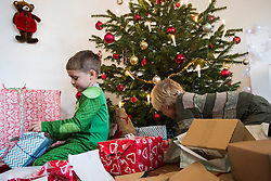 Children opening Christmas gift at home