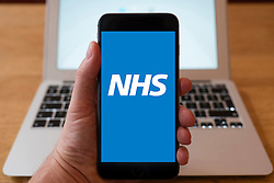 Using iPhone smartphone to display logo of NHS , National Health Service website