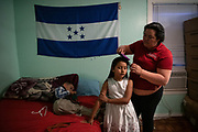 Irma, an asylum seeker from Honduras, prepares children Suany and Jesus for church at home in Fort Worth, Texas, U.S., May 12, 2019.