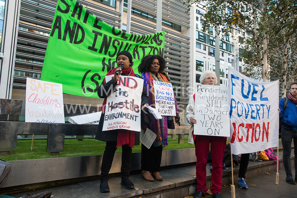 London, UK. 17 October, 2019. Geraldine Takundwa of the All African Women's Group (AAWG) addresses campaigners from Fuel Poverty Action (FPA), residents in uninsulated homes and climate activists protesting outside the Ministry of Housing, Communities and Local Government (MHCLG) before delivering a letter signed by FPA, 80 organisations, trade unions and MPs in just ten days precisely one year after a strongly worded letter about the urgency of recladding flammable buildings and insulating those that are cold was delivered to the Government department. Commitments made by the MHCLG in response to the original letter have not been met. Credit: Mark Kerrison/Alamy Live News