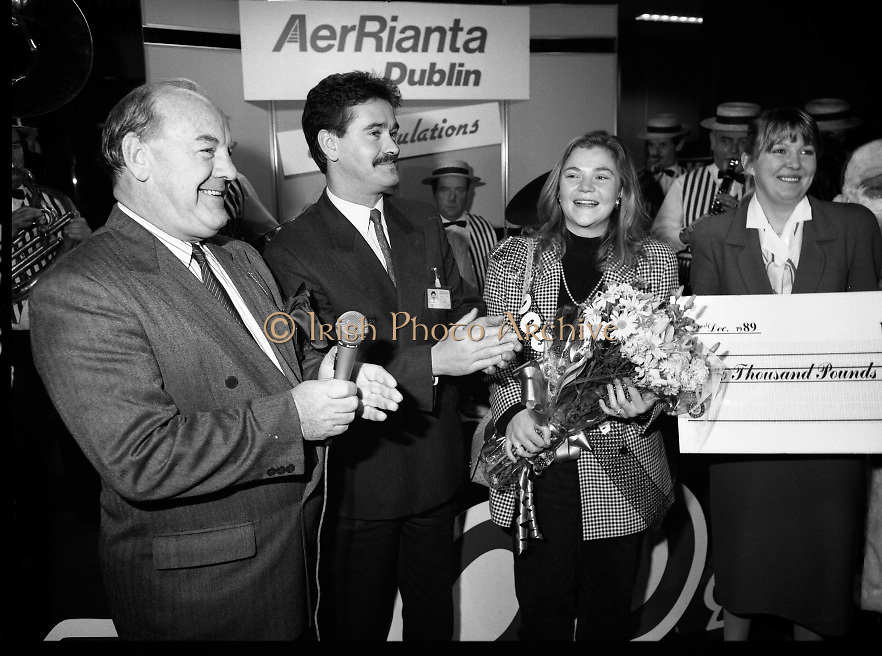 5,000,000th Passenger Through Dublin Airport. (T12).1989..22.12.1989..12.22.1989..22nd December 1989..The date,Friday,22nd December 1989 will be remembered as an historic day in Irish Aviation as Aer Rianta celebrated the 5millionth passenger to fly through Dublin Airport in one year. The Lucky passenger, Nicola Wynne, arrived at 10AM from Germany and was welcomed to Dublin Airport by General Manager,Tom Cullen...Image shows a stunned, Nicola Wynne,Boyle, Roscommon, celebrating her lucky day as she is presented with a cheque for £2000 as she had become the 5millionth passenger through Dublin Airport in 1989. Tom Cullen, General Manager, Aer Rianta and Terence McGowan,Manager Airport Services,Delta Airlines are included in the picture.