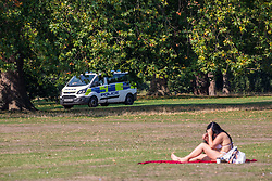"© Licensed to London News Pictures. 15/09/2020. London, UK. A sunbather enjoys the warm sunshine this morning as Police vans patrol Hyde Park enforcing the ""Rule of Six"" as the mini-heatwave continues in the South East of England with highs of 29c. Prime Minister Boris Johnson announced last week that gatherings of more than six people will be banned from Monday (yesterday) in the hope of reducing the coronavirus R number. The Rule of Six has already become unpopular with MPs and large families for being too strict. Photo credit: Alex Lentati/LNP"