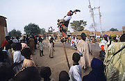Acrobat on stilts in a rural village during the Kano Durbar Fantasia..The Durbar Fantasia, is the moment where The Husa residents of Kano wear traditional dress, their local leaders and chiefs mount horses, and together with their militias display allegiance and homage to their leader, the Emir of Kano. This takes place after Ramadan. The Emir is Kano's State official political and economic feudal leader, everyone seeks to be in his pleasure, otherwise they reap the consequences..Kano is the largest Muslim Husa city, under the feudal, political and economic rule of the Emir. Kano and the other eleven northern states are under Islamic Sharia Law which is enforced by official state apparatus including military and police, Islamic schools and education, plus various volunteer Militia groups supported financially and politically by the Emir and other business and political bodies. 70% of the population live below the poverty line. Kano, Kano State, Northern Nigeria, Africa