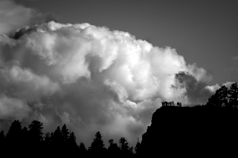 Spectators stand on the overlook at Inspiration point on a backdrop of massive clouds at Bryce Canyon, Utah.