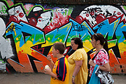 Family walk past grafitti at Brick Lane for the Sunday Market. Many people come to sell their cast-off clothes and belongings to raise some cash. Official stalls selling clothers, food and all manner of crafts and junk make up the mainstay of the market though. These unofficial sellers though give the market it's unique atmosphere. This market is a weekly event in London's East End.